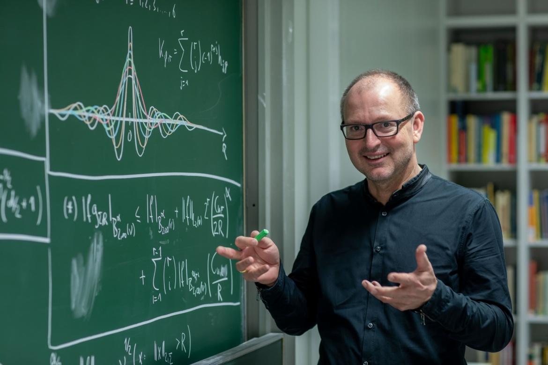 Prof. Hesse vor einer Kreidetafel mit grüner Kreide in der rechten Hand