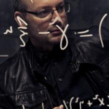 Christian Hesse hinter einer Glastafel mit mathematischen Formeln