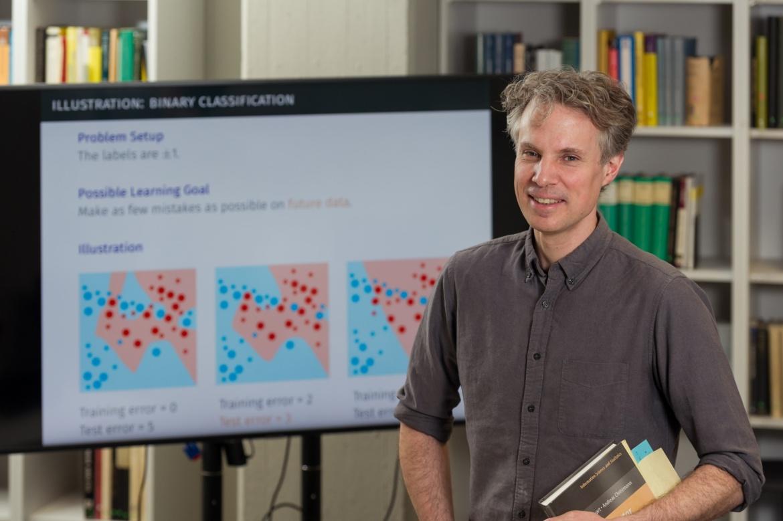 Prof. Steinwart vor einem Monitor mit seiner Forschung