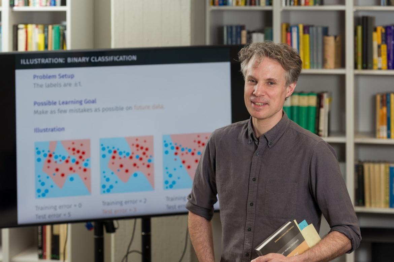 Prof. Steinwart mit Buechern in der Hand vor einem grossen Monitor
