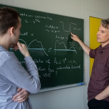 Thomas Hamm and Ingo Steinwart in front of a chalkboard with mathematical formulas